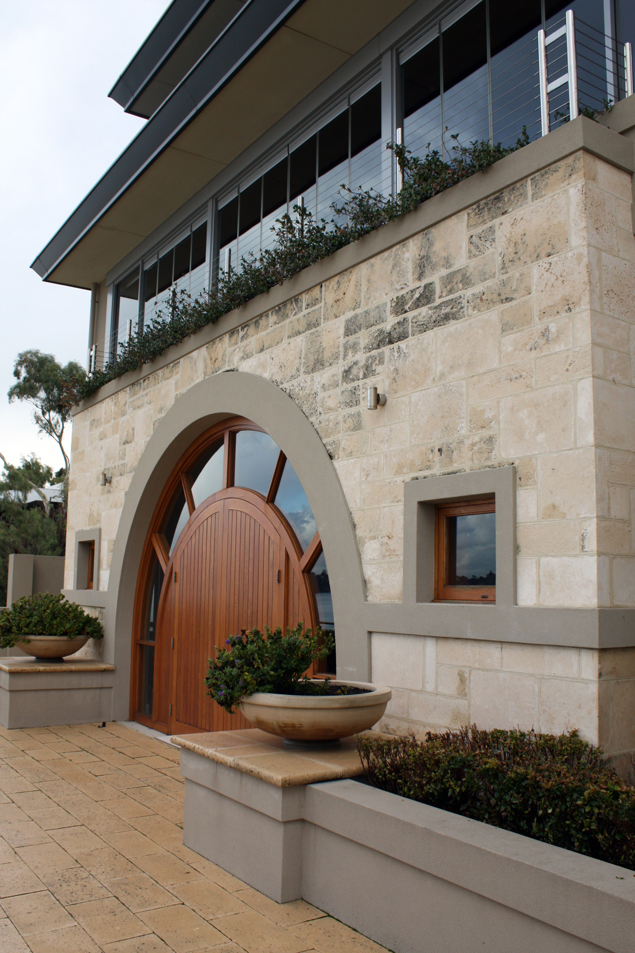 External house entrance with limestone wall and large wood wall